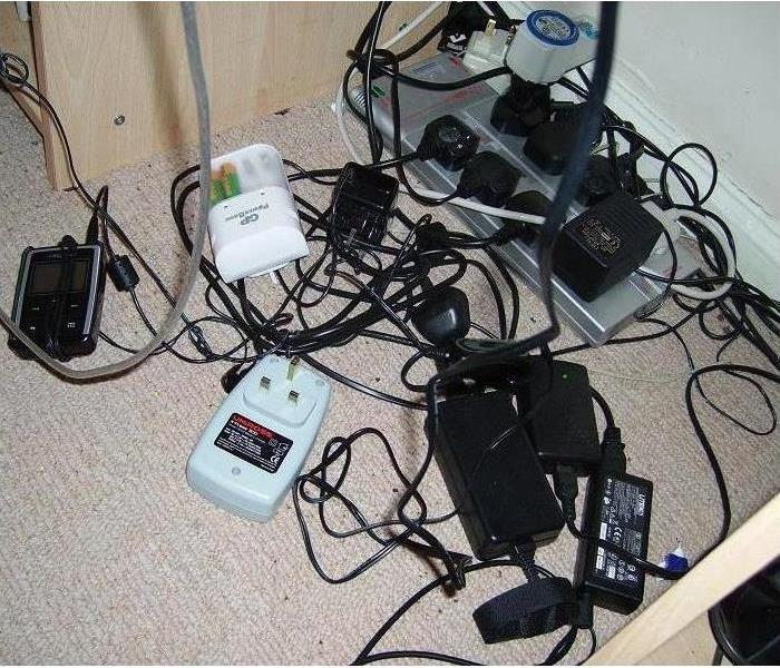 A bunch of cords plugged into an outlet.